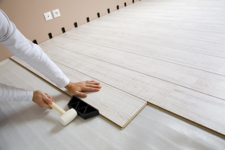 laminate flooring:  Worker laying a floor with laminated flooring boards