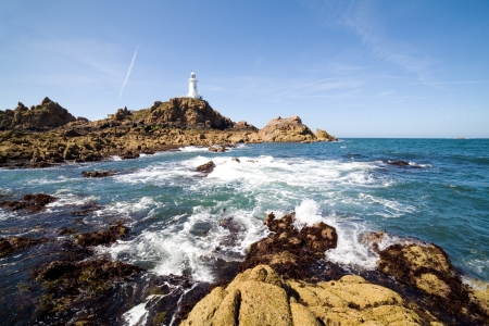 rough sea: Corbiere Lighthouse and the rocky coast in Jersey, The Channel Islands Stock Photo