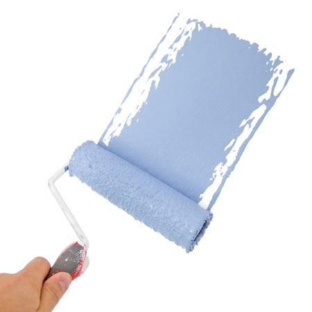 painters: Painter holding a roller, painting in blue Stock Photo