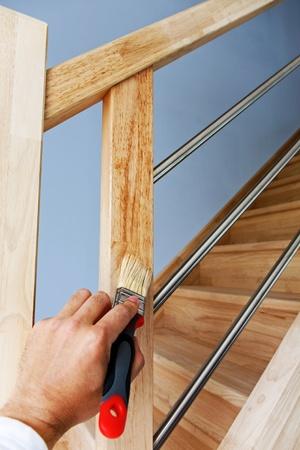 손으로 나무 계단에 보호 오일을 적용 스톡 콘텐츠