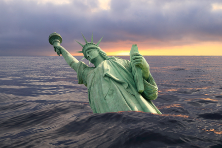 Statue of Liberty sinks in the ocean in the sunset Stock Photo