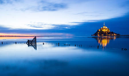 Mont-Saint-Michel sunset with deep blue water and clear reflections, Normandy, France