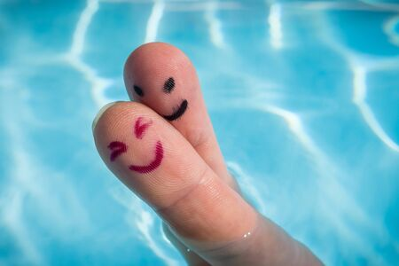 Happy finger couple for a hug in the swimming pool