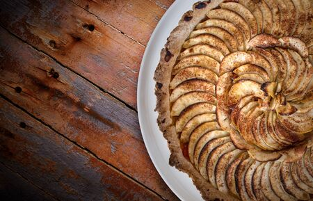 Traditional french apple tart over brown planks background