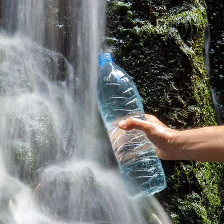 Mineral water taken in the nature, filling the bottle