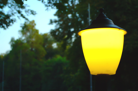 Lyrical background, small street lantern shining bright yellow light, trees and pillars in bokeh style (out of focus)
