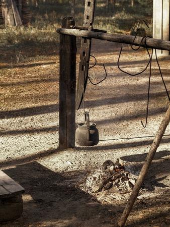 under fire: hervidor de agua colgando bajo chimenea Foto de archivo