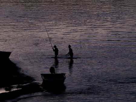catchlight: outlines of  fishing boys at river Stock Photo