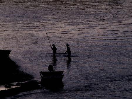 streifzug: Umrisse von Fischerjungen in Fluss
