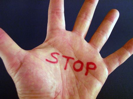 war crimes: stop sign in palm Stock Photo