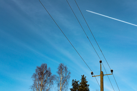 A plane in high flight above tree tops and telephone lines