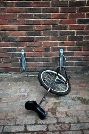 A unicycle chained to a bicycle rack photo