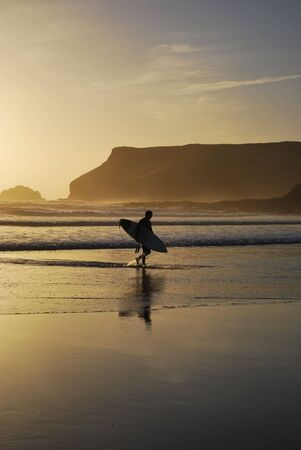 cornwall: A surfer leaves the surf as the sun sets at Polzeath Beach in Cornwall, UK.