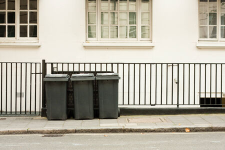 A row of three domestic wheelie bins in the street photo