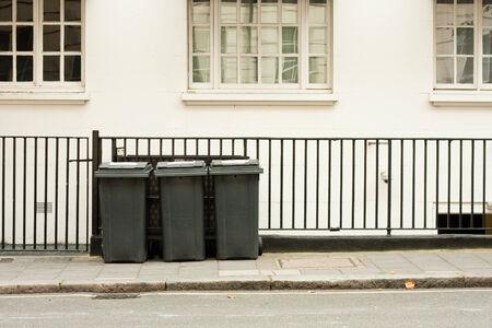 A row of three domestic wheelie bins in the street Stock Photo