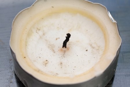 tealight: A white tealight candle with a burnt wick and melted wax