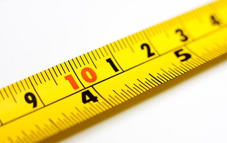 millimetres: Close-up of a yellow tape measure on a white background