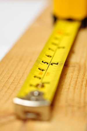millimetres: A yellow tape measure laid out on a block of wood
