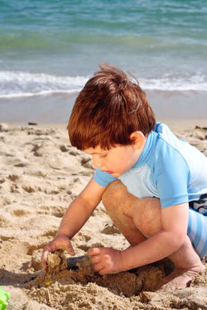 3 year old boy: A young 3 year old boy playing with the sand on a beach