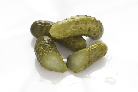 gherkins: A chopped and two whole gherkins on a white background