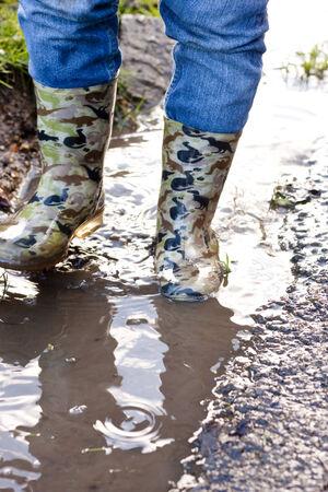 wellie: Wellie clad feet walking through a muddy puddle