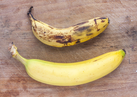 color photographs: A rotten and a fresh ripe banana side by side on a mottled wooden surface Stock Photo