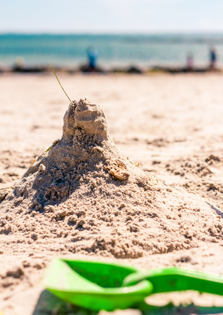 sand castle: A basic looking sand castle on the beach with a green spade in the foreground Stock Photo