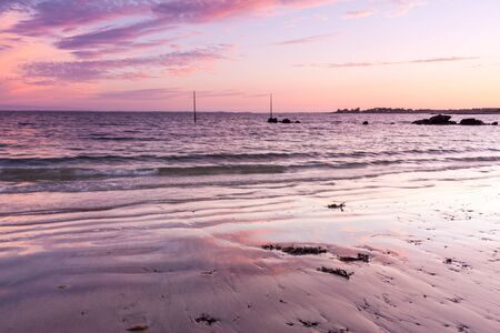 Fiery skies during sunset at Plage de Kervillen, Brittany, France.