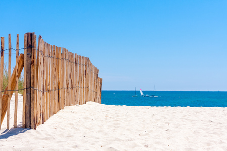 fence: A wooden fence on a white sandy beach on a sunny day with clear blue sky