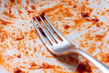 A fork on an empty used white plate with remains of tomato sauce Banco de Imagens