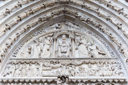 Historic decorations & ornaments on church with perfect detail on a large wooden door.