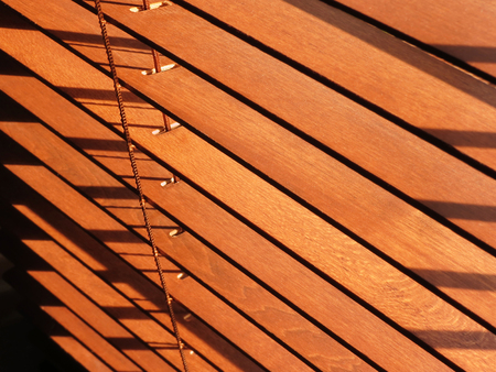 Open brown wooden blinds, with sunlight shining through