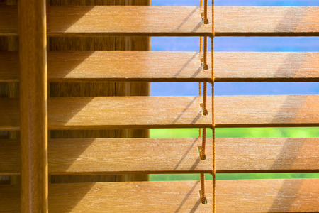 Brown wooden blinds that are slighlty open showing blue sky on a bright sunny day Reklamní fotografie