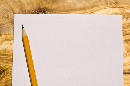 aerial view of a sheet of paper with a yellow pencil on a wooden desk Reklamní fotografie