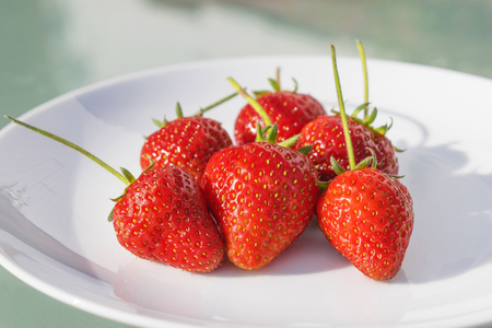 Freshly picked ripe strawberries served on a white plate