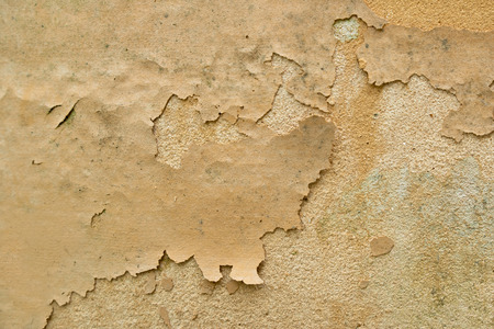 Old cracking paint on a stained concrete wall
