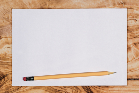 Paper and pencil on a wooden desk, viewed from above with copy space Reklamní fotografie