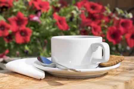 Cup of coffee served on a wooden wood table with a white napkin, spoon and biscuit with a blurred floral background