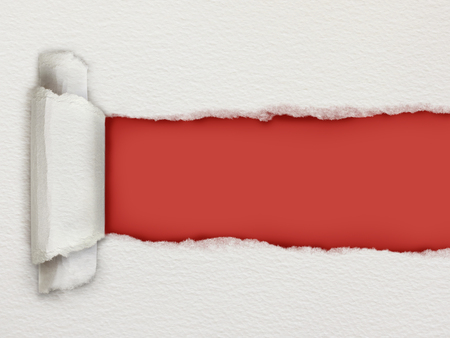 Torn piece of watercolour paper revealing a red background for copy space Reklamní fotografie