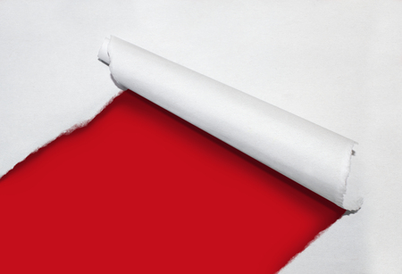 Torn paper curl revealing a red background for copy space