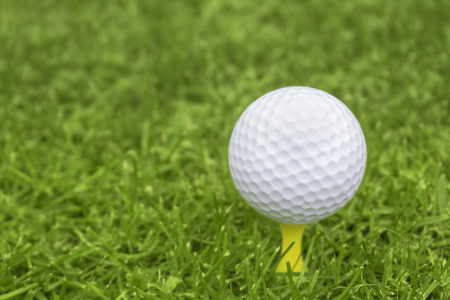 Golf ball on a yellow tee with a blurred background for copy space Reklamní fotografie