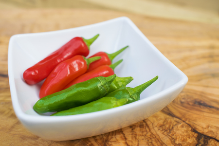 Close up of a green chili pepper in a white bowl on a wooden table