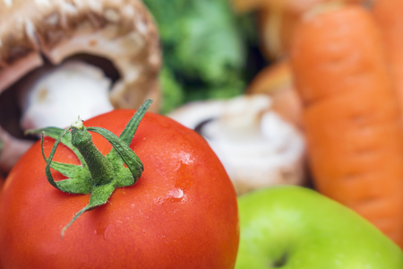 Close up of a fresh juicy ripe tomato with a blurred background of fruit and vegetables for copy space