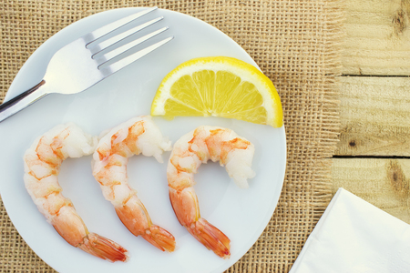 Close up of a group of shrimps and a lemon served on a white plate, viewed from above Reklamní fotografie
