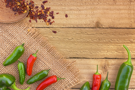 red and green chilli peppers on a rustic background viewed from the top with copy space