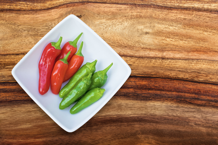Group of fresh chilis in a white bowl viewed from the top with copy space