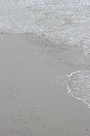 sand mold: Surf washing up on flat beach