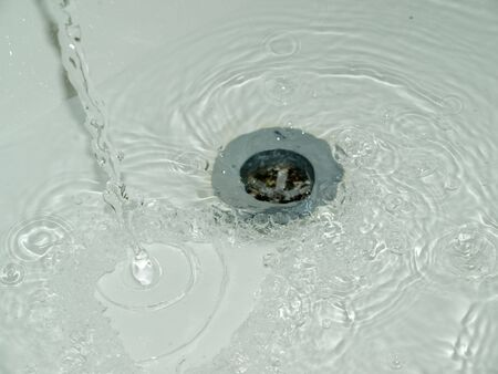 wasted: Water being wasted and poured down a plughole