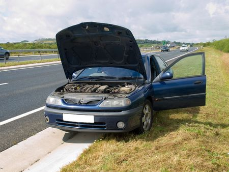 car side: Broken down car on the side of a busy road Stock Photo