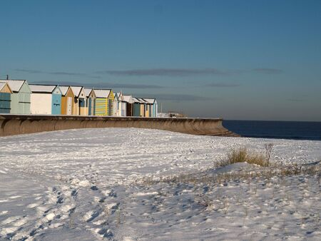 A row of colourful beach huts in the snow photo